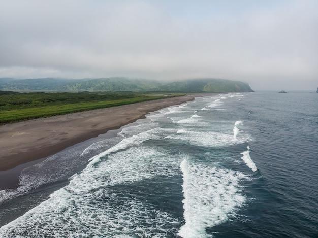 太平洋の暗いほぼ黒色の砂浜。石の山と黄色い草が背景にあります。 Premium写真