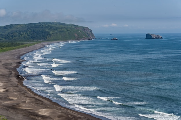Dark almost black color sand beach of pacific ocean. stone mountains and yellow grass are on a background. Premium Photo