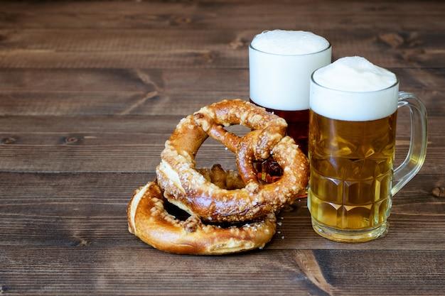 ダークとライトのビール、木のプレッツェル Premium写真