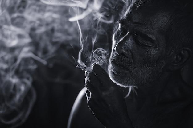 喫煙している老人の暗くて不機嫌なショット Premium写真