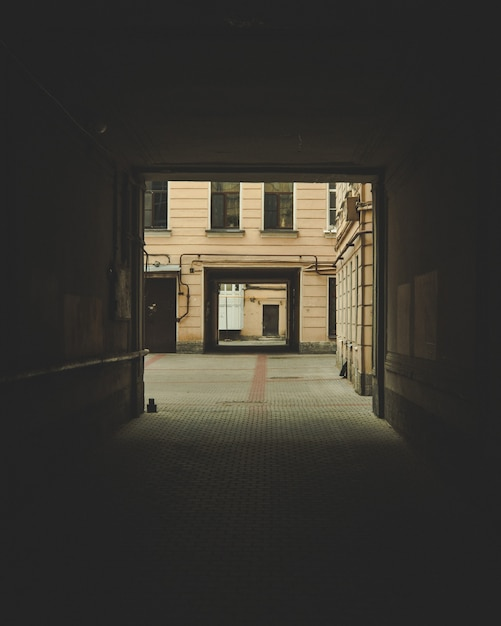 Dark archway with a building visible in the background Free Photo