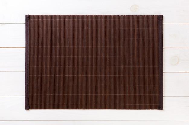 Dark bamboo mat on white wooden background Premium Photo