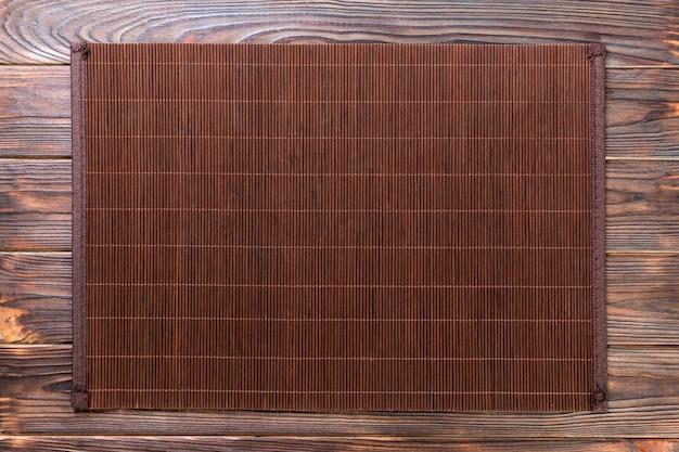 Dark bamboo mat on wooden background Premium Photo
