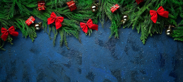 Dark blue background empty space. christmas tree branches and decoration. banner Premium Photo