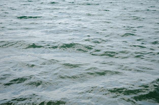 水面の暗い青色の背景。海の水面のテクスチャ。深海の波 Premium写真