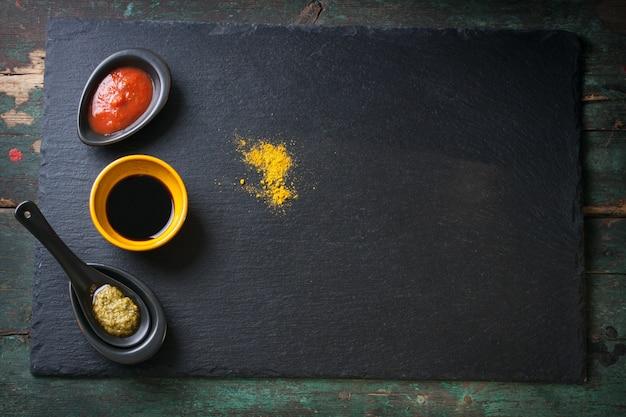 Dark board with condiments Free Photo