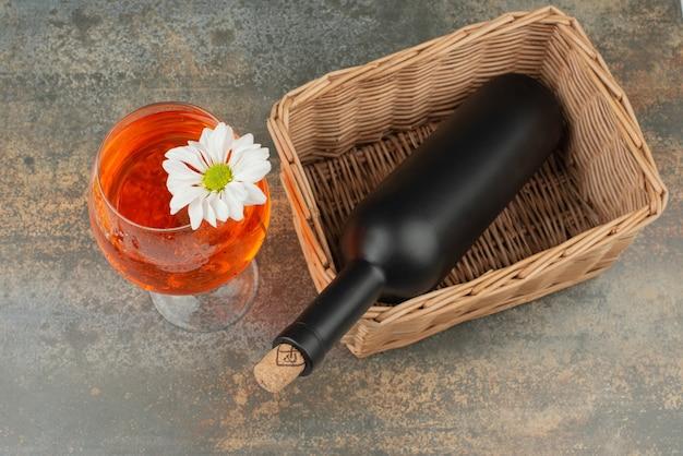 Bottiglia scura sul cestello con un bicchiere di succo su sfondo marmo. foto di alta qualità Foto Gratuite
