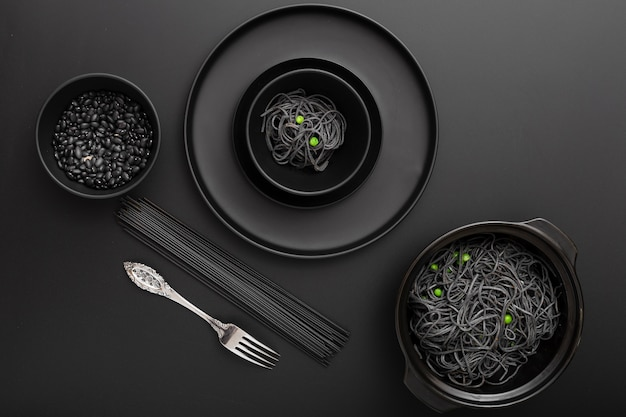 Dark bowls with pasta and beans on a black table Free Photo