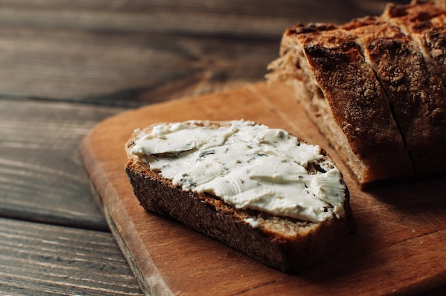 Dark bread is spread with cottage cheese with herbs in a cut on a wooden board on a wooden table in a rustic style. Premium Photo