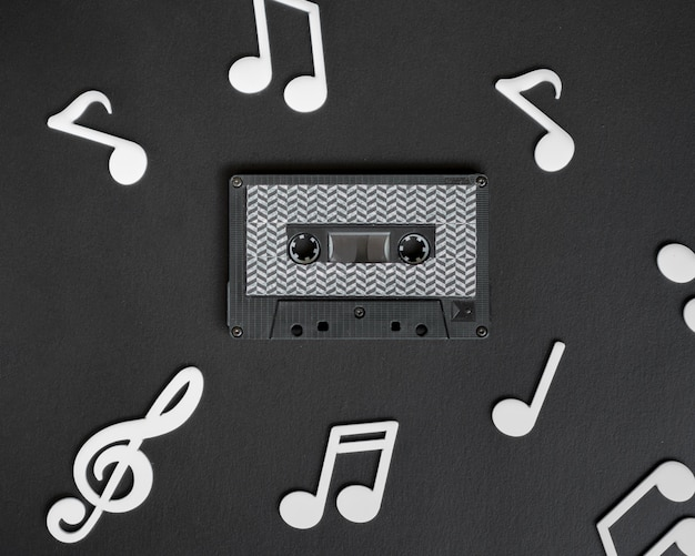 Dark cassette tape with white musical notes surrounding it Free Photo