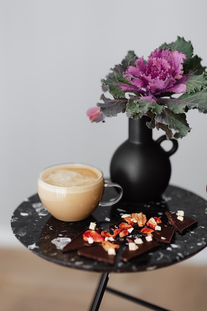 Dark chocolate brittle and milk tea on a black table with an ornamental kale flower Free Photo