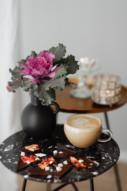 Dark chocolate brittle and milk tea on a black table with an ornamental kale flower Premium Photo