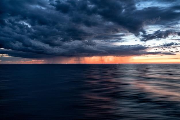海の暗い水に沈む夕焼け空の暗い雲 無料写真