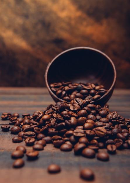 Темные кофейные зерна в миске на коричневом столе Бесплатные Фотографии