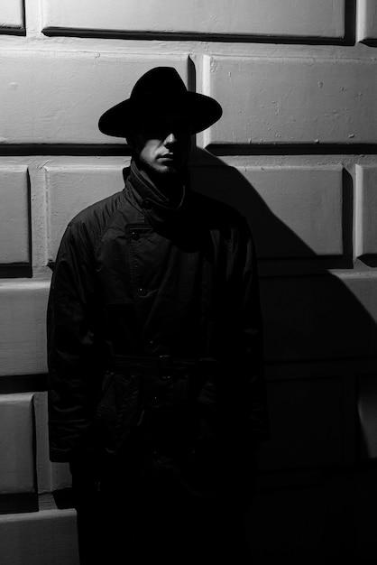 ノワールスタイルの路上で夜の帽子とレインコートを着た男の暗いドラマチックなシルエット Premium写真