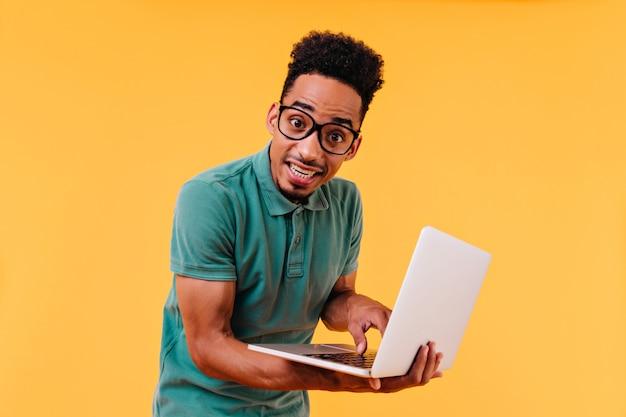 Dark-eyed international student posing with white laptop. indoor photo of male freelancer typing on keyboard. Free Photo