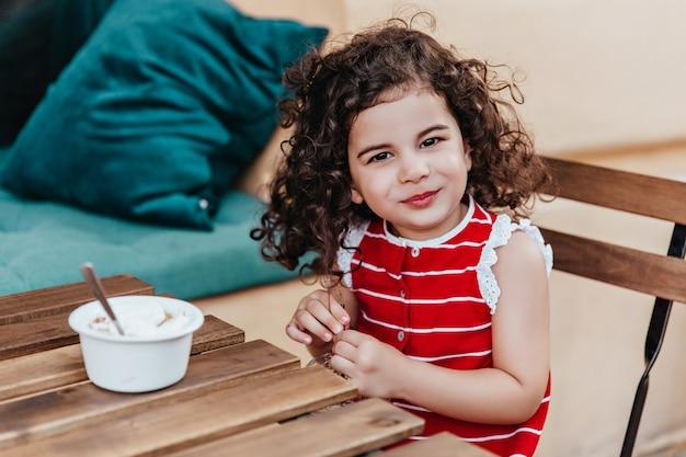카페에서 디저트를 즐기면서 포즈를 취하는 검은 눈의 아이. 아이스크림을 먹고 웃는 어린 소녀의 야외 사진. 무료 사진