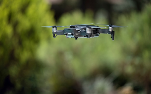 Dark grey drone flying over a green background Premium Photo