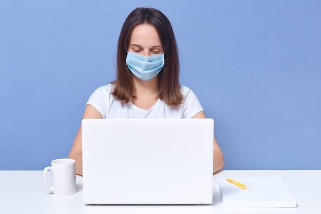 ラップトップ画面の前で働くカジュアルなtシャツと医療用防護マスクを身に着けている暗い髪の女性は、集中しているように見えます。 無料写真