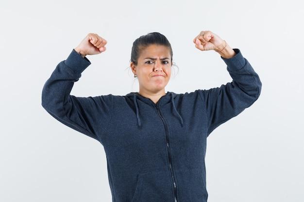그녀의 근육을 보여주고 강력하게 보이는 동안 그녀의 팔을 올리는 재킷에 검은 머리 여자 무료 사진
