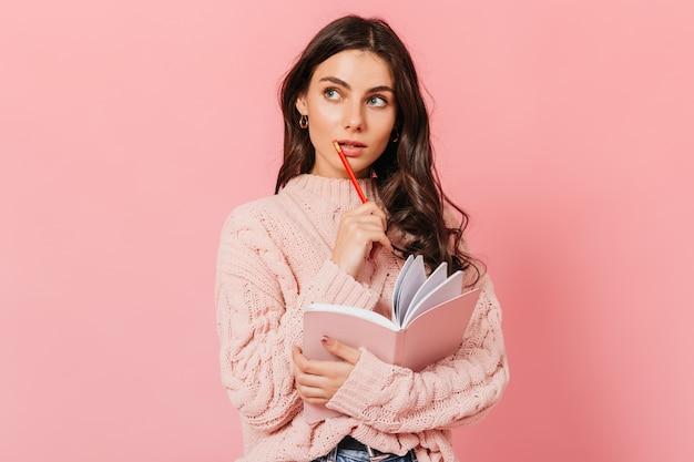 ニットのセーターを着た黒髪の女性が思慮深く見上げる。女性は新しい本に何を書くべきかを考えます。 無料写真