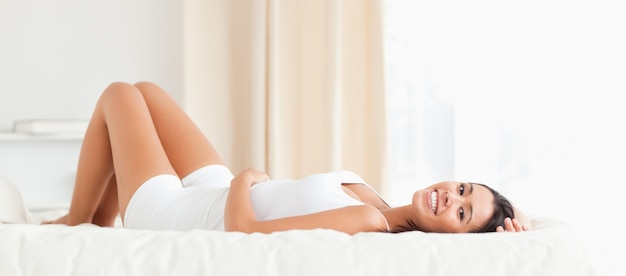 Dark-haired woman lying on bed Premium Photo