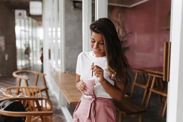 Темноволосая женщина с улыбкой помешивает клубничный йогурт Бесплатные Фотографии