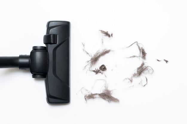 바닥을 청소하는 동안 사용되는 현대 진공 청소기의 어두운 머리. 프리미엄 사진