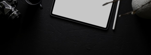 Dark modern workspace with mock-up tablet, camera, decorations on black desk Premium Photo