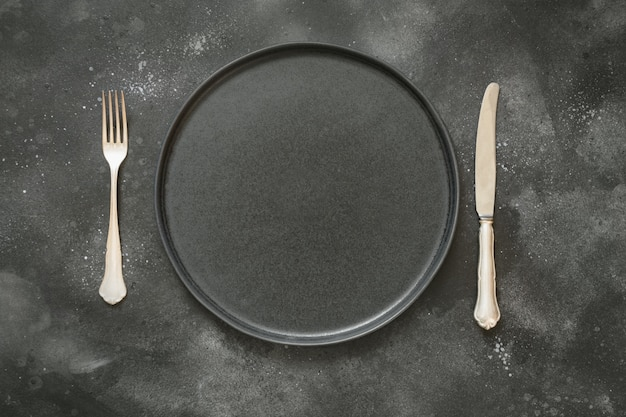 Dark place setting on black table. top view. Premium Photo
