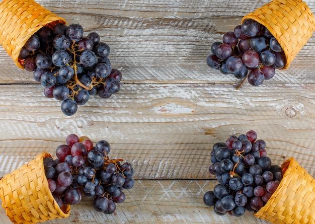 フラットの木製の背景に枝編み細工品バスケットの濃い赤ブドウを置きます。 無料写真