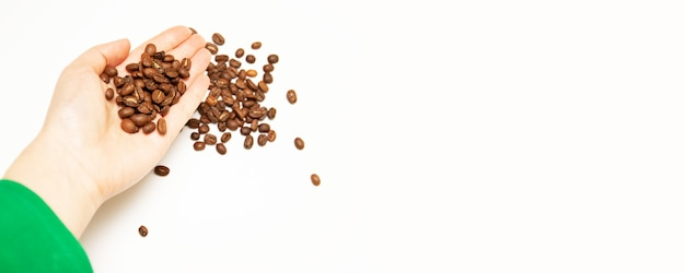 Dark roasted coffee beans in the farmer's hand with macro view. Premium Photo