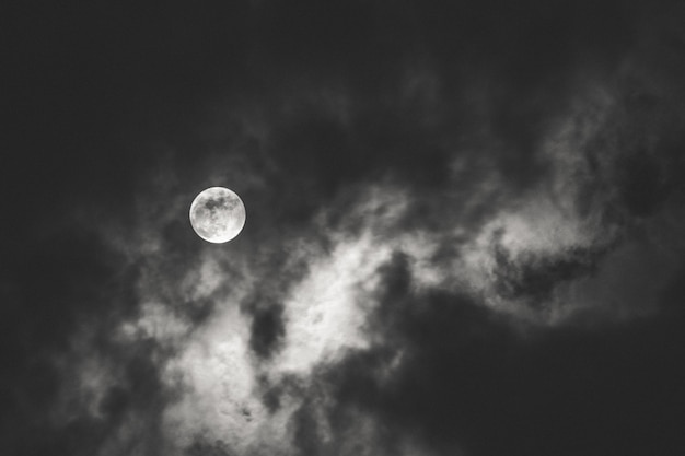밤 동안 구름 뒤에 빛을 확산 보름달의 어두운 샷 무료 사진