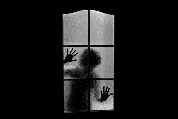 Dark silhouette of girl behind glass. locked alone in room behind door on halloween in grayscale. nightmare of child with aliens, monsters and ghosts. evil in home in monochrome. inside haunted house. Premium Photo
