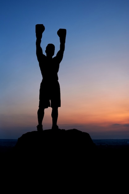 Dark silhouette of male boxer posing outdoors in summer Premium Photo