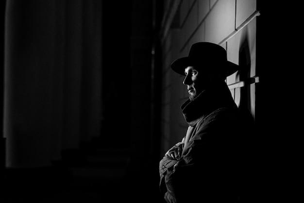 犯罪ノワールスタイルで夜に帽子と彼の顔に傷跡を持つレインコートを着た男の暗いシルエット Premium写真