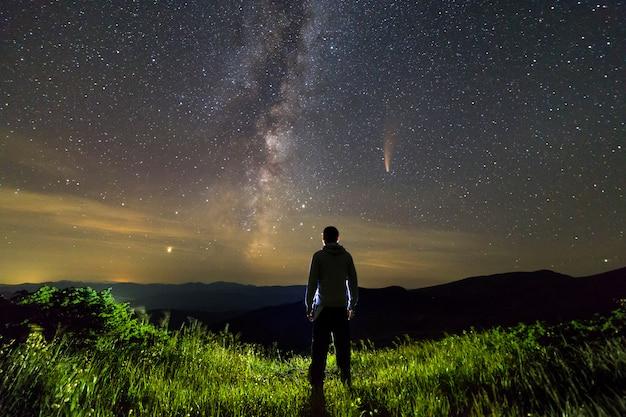 夜空に山に立っている男の暗いシルエット。 Premium写真