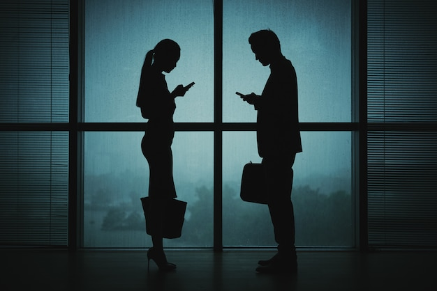 Dark silhouettes of man and woman in business attire standing by window at night with smartphones Free Photo