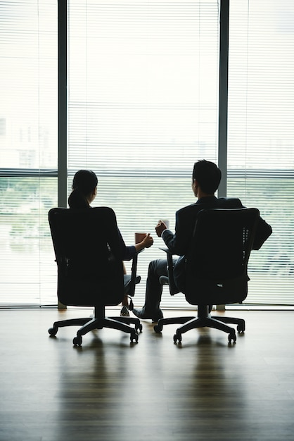 Dark silhouettes of man and woman sitting with mugs in office chairs in front of window Free Photo