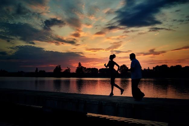 Dark silhouettes of running girl and senior man while sunset near lake. Premium Photo