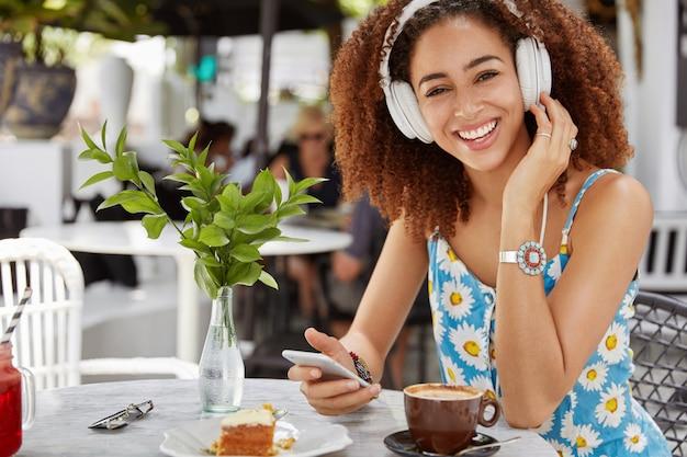 ダークスキンのアフリカ系アメリカ人女性は、お気に入りの曲の完璧なサウンドをヘッドフォンで楽しんだり、携帯電話に接続したり、プレイリストでオーディオを選択したり、レストランでコーヒーを飲んだり、デザートを食べたりします。 無料写真