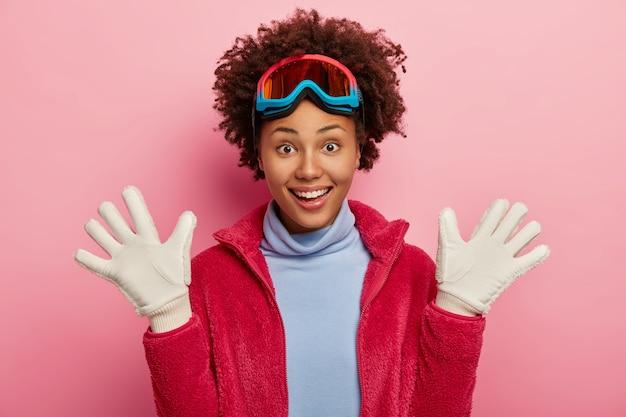 어두운 피부를 가진 여성 스키어가 흰 장갑을 끼고 손바닥을 들어 올리고, 스노 보드를 즐긴 후 즐겁게 웃으며, 보호 마스크, 터틀넥과 빨간 재킷을 착용하고, 겨울 방학을 보내고, 분홍색 배경에 고립 된 무료 사진