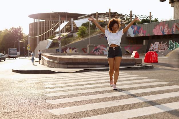 浅黒い肌の女の子が街を歩いて楽しんでいます Premium写真