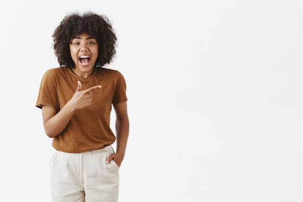 Темнокожая девушка с афро-прической в стильной коричневой футболке с удовольствием проводит время, радостно смеясь и указывая на что-то смешное, чтобы правильно держать руки в кармане Бесплатные Фотографии