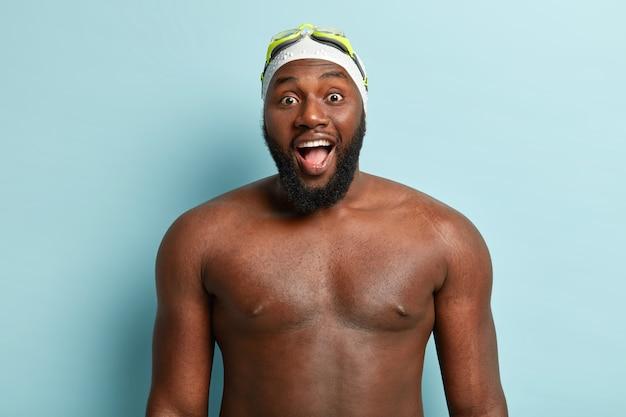 裸の体を持つ暗い肌のハンサムな男は、泳ぐ準備をし、特別な帽子とゴーグルを着用し、口を大きく開いたままにします 無料写真