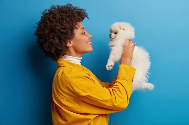 浅黒い肌の女性は唇を丸く保ち、愛らしいペットにキスしたい、小さな子犬と遊ぶ 無料写真