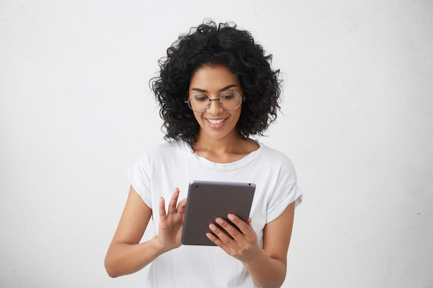 Dark-skinned smiling charismatic and beautiful female student holding modern gadget, using tablet for video call with her friends, watching funny videos or doing homework, chatting Free Photo