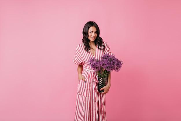 Темнокожая женщина уверенно в розовой комнате. дама в длинном сарафане держит вазу с цветами. Бесплатные Фотографии
