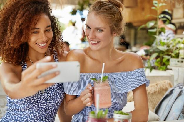 暗い肌の若い女性と友人は前向きな表情を持ち、自撮りをし、スムージーを飲み、カフェテリアでレクリエーションの時間を過ごします。人、レクリエーションの時間とライフスタイルのコンセプト 無料写真