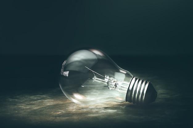 Dark tone lightbulb lamp on the floor dramatic background concept. Premium Photo